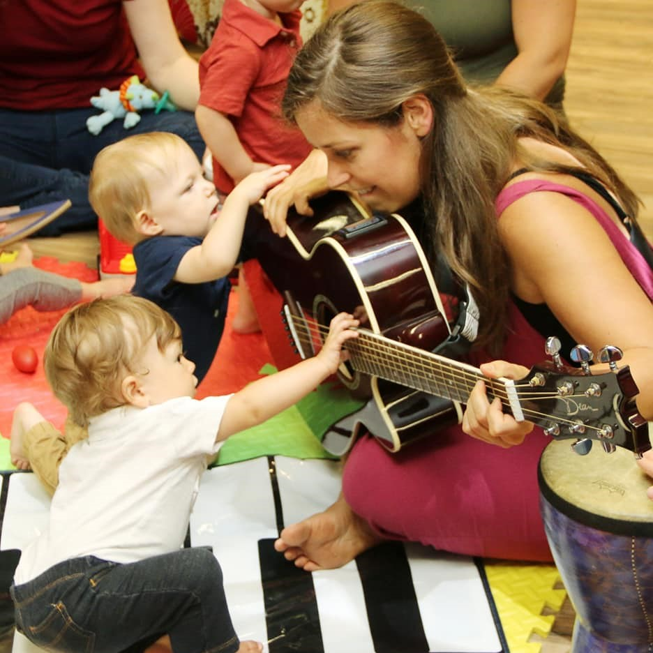 Individual seated on the floor playing guitar while infants are encouraged to explore the instrument