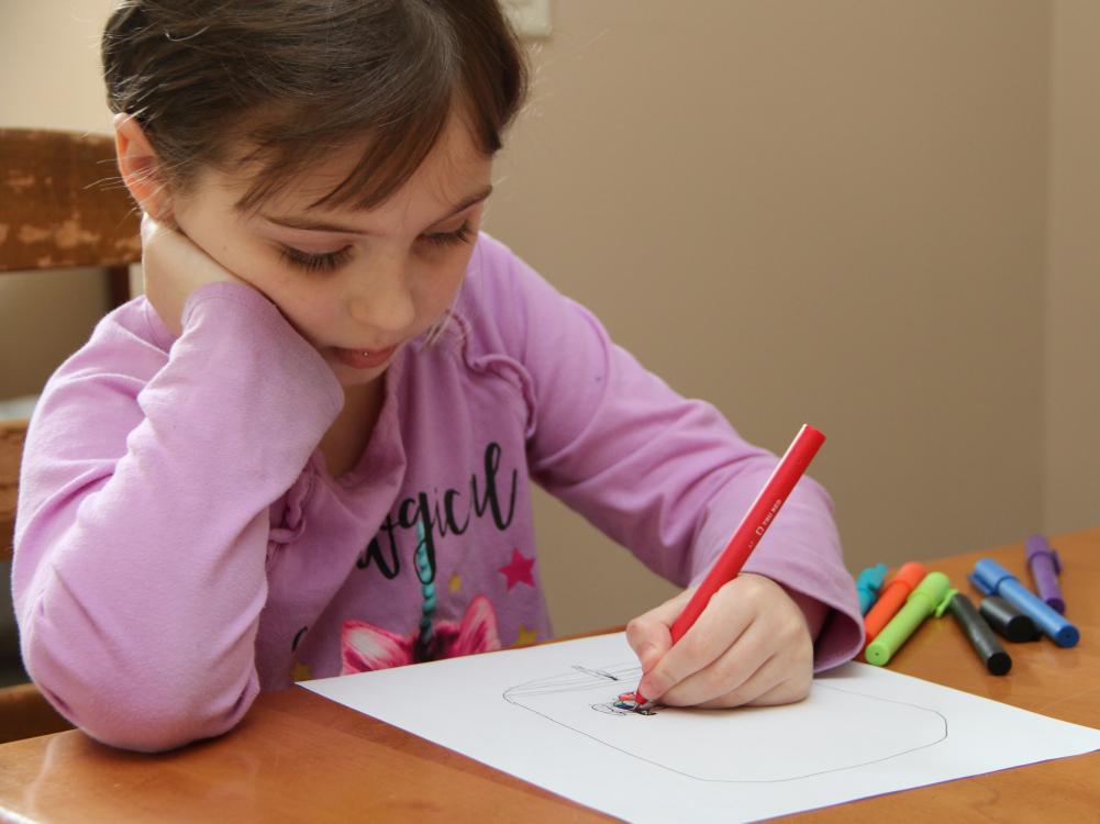 School age child completing worksheet