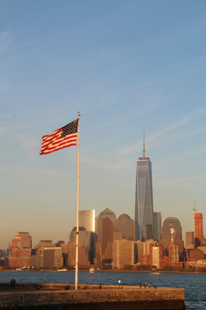 American Flag with cityscape in background